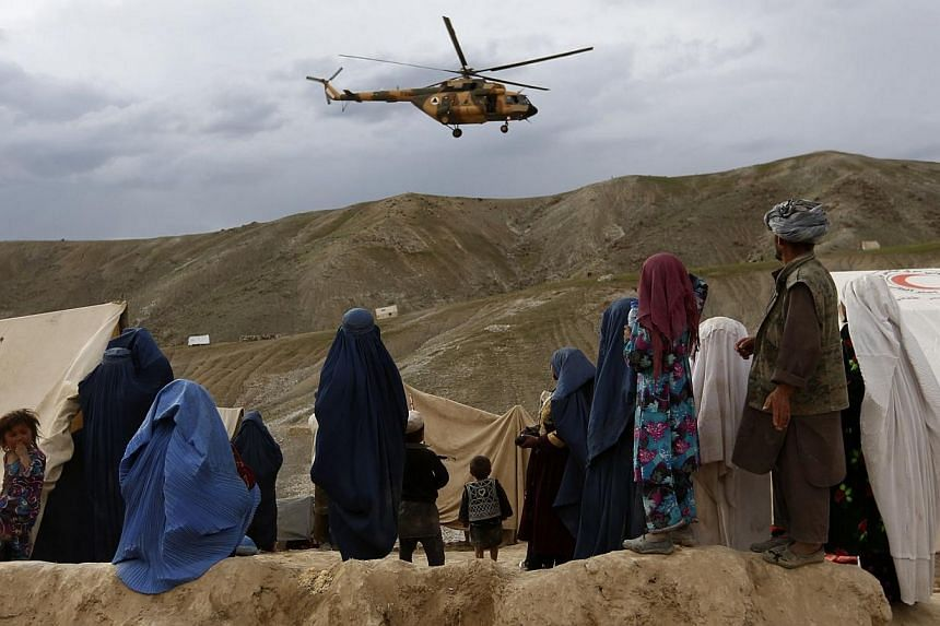 A military helicopter flies as displaced Afghans stand near the site of a landslide at the Argo district in Badakhshan province on May 5, 2014.As many as 2,700 people may be buried after a landslide in the Ab-e-Barak village in Badakhshan provi