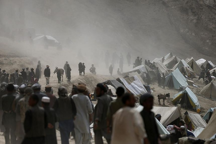 Afghan villagers gather near the site of a landslide at the Argo district in Badakhshan province.As many as 2,700 people may be buried after a landslide in the Ab-e-Barak village in Badakhshan province in Afghanistan on May 2. -- PHOTO: REUTERS