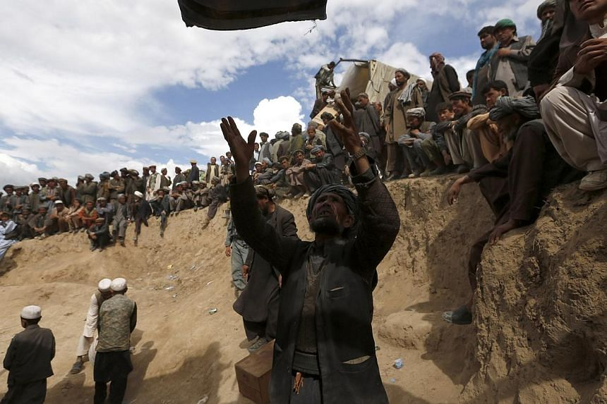 An Afghan villager receives aid near the site of a landslide at the Argo district in Badakhshan province on May 5, 2014.As many as 2,700 people may be buried after a landslide in the Ab-e-Barak village in Badakhshan province in Afghanistan on M