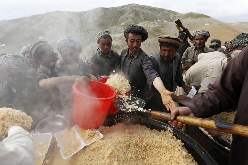 Afghans wait to get their lunch near the site of a landslide at the Argo district in Badakhshan province on May 5, 2014.As many as 2,700 people may be buried after a landslide in the Ab-e-Barak village in Badakhshan province in Afghanistan on M