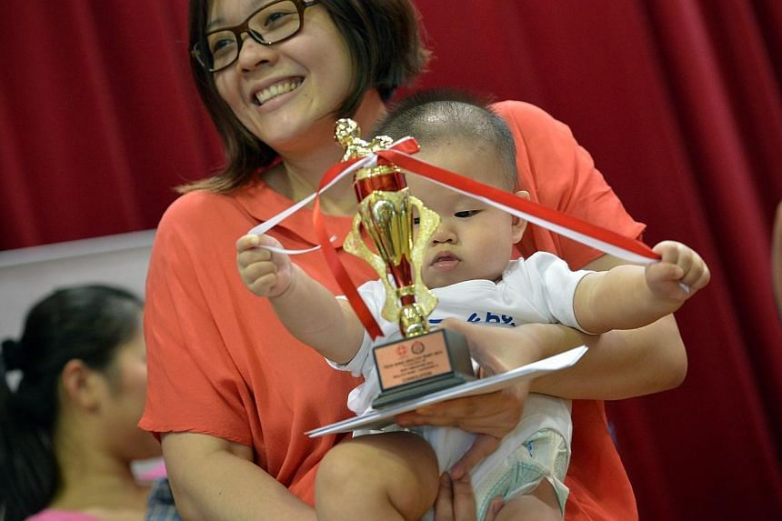 Carried by his mother, Mdm Sharon Wang, 29, Tyler Li, 7 months, plays with the ribbons on the trophy after coming in 5th at the Healthy Baby contest of the Teck Ghee Baby Show held at Teck Ghee CC.Singapore is the best place in Asia to be a mot