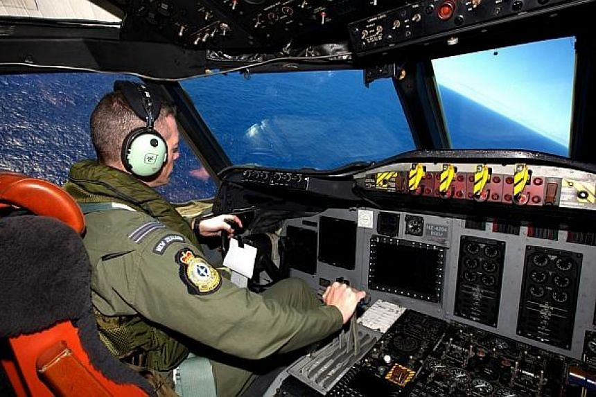 Royal New Zealand Air Force Captain Flight Lieutenant Timothy McAlevey sits in the cockpit of a P3 Orion maritime search aircraft as it flies over the southern Indian Ocean looking for debris from missing Malaysia Airlines Flight MH370 on April 11, 2