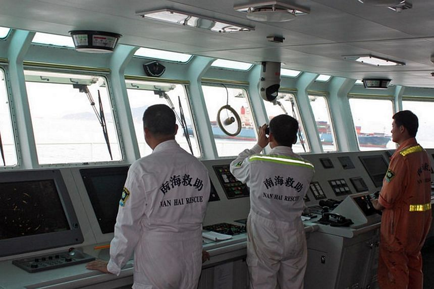 This handout photo taken and received by the Nanhai Rescue Bureau (NRB) on May 5, 2014 shows NRB rescuers searching for survivors in the water after the Marshall Islands-registered MOL Motivator collided with a Chinese cargo ship, the Zhong Xing 2, o