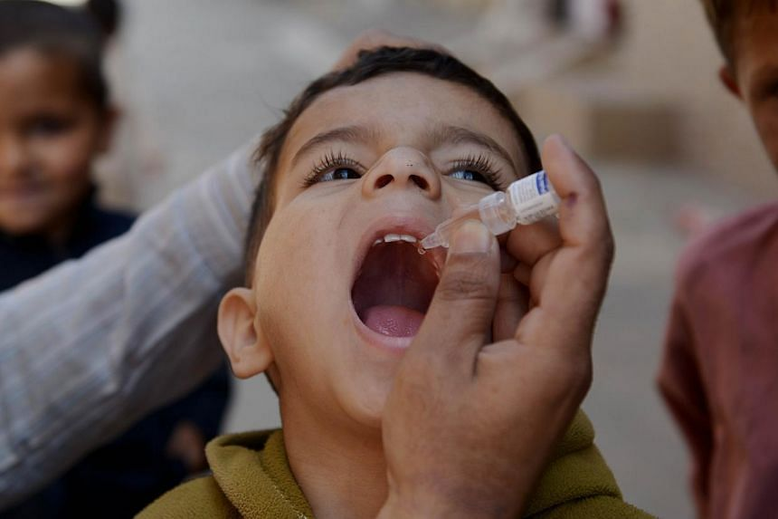 A Pakistani child receives polio vaccination drops from a health worker in Rawalpindi in the northern part of the country on April 8, 2014.Pakistan will set up mandatory polio immunisation points at its international airports in response to rec