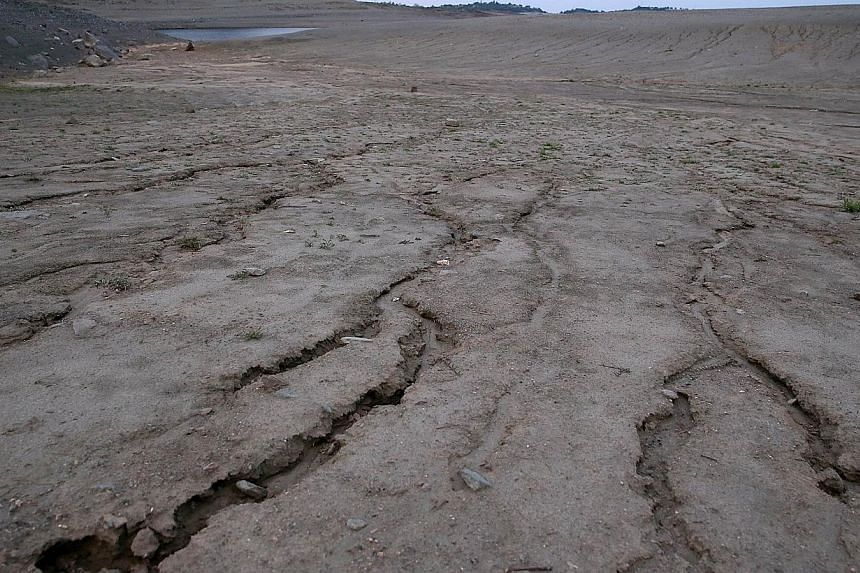 Dry and cracked earth is visible on what used to be the bottom of Folsom Lake on March 20, 2014 in El Dorado Hills, California.The Obama administration will release an updated report on Tuesday showing how climate change touches every part of t
