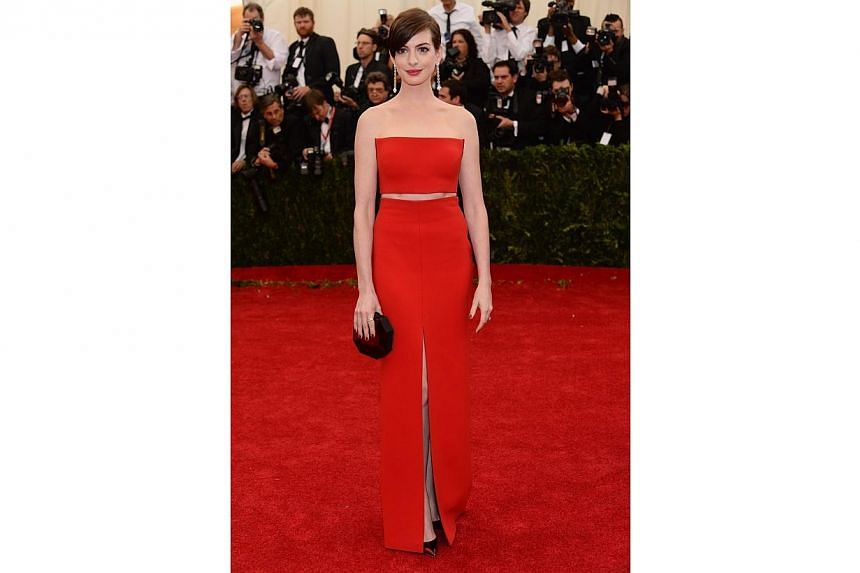 HOT OR NOT: It could take a lot or very little to pull off a red dress on the red carpet. Anne Hathaway did so by baring just tiny slivers of skin in a red Calvin Klein gown. -- -- PHOTO: AFP