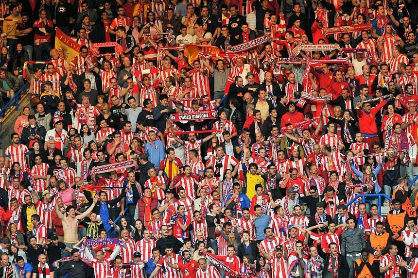 Atletico Madrid fans cheer during the UEFA Champions League semi-final second leg football match between Chelsea and Atletico Madrid at Stamford Bridge in London on April 30, 2014.European football's governing body Uefa on Monday blasted raci