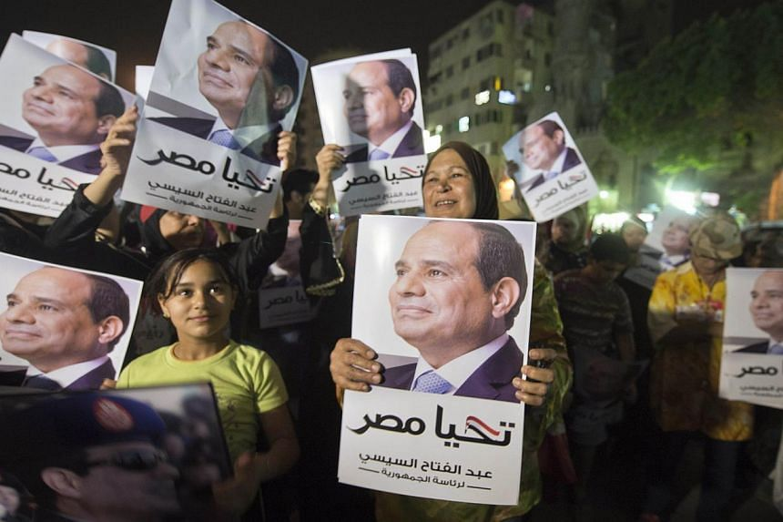 Egyptian supporters of Egypt's former army chief Abdel Fattah al-Sisi hold his portraits as they watch him on a screen from the street in downtown Cairo on May 5, 2014, during his first television interview.Egypt's ex-army chief and leading p