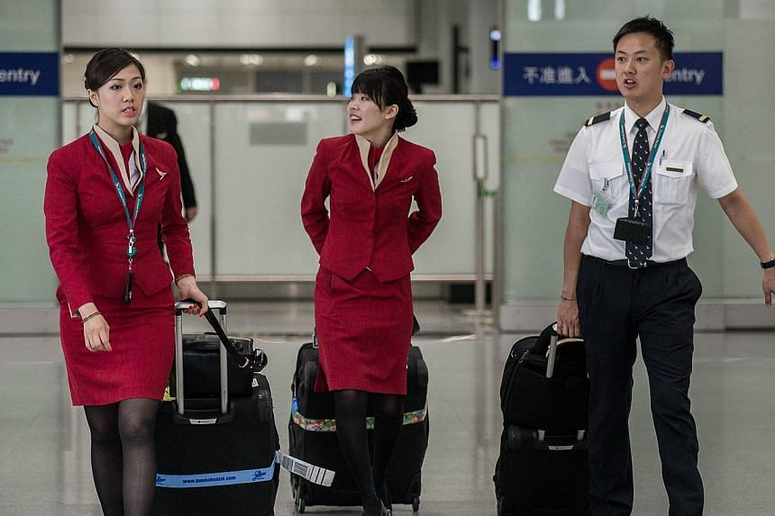 Cathay Pacific flight attendants want the Hong Kong airline to redesign their uniforms because they are too revealing and may provoke sexual harassment, a union has said. -- PHOTO: AFP