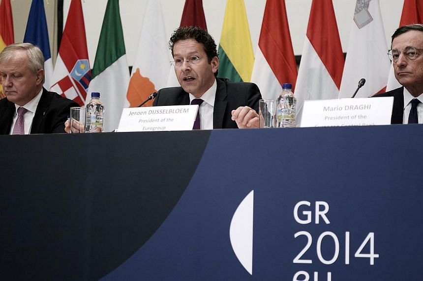 Vice President of the European Commission Olli Rehn (left), President of the Eurogroup an Finance Minister of the Netherlands Jeroen Dijsselbloem (centre) and President of the European Central Bank Mario Draghi (right) give a press conference of the