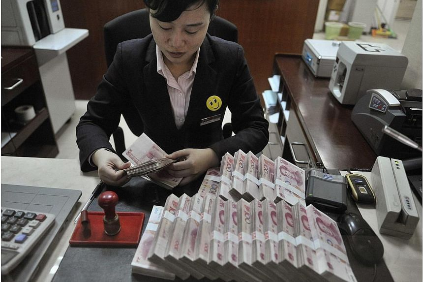 A clerk counts 100 Chinese yuan banknotes at a branch of China Merchants Bank in Hefei, Anhui province on March 17, 2014. -- FILE PHOTO: REUTERS