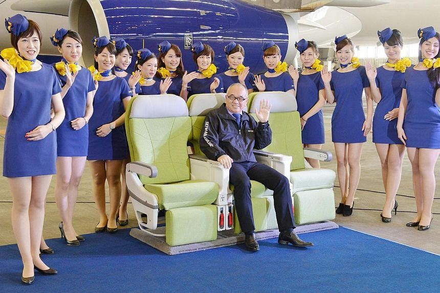 The president of Japan's Skymark Airlines, Shinichi Nishikubo (centre), and flight attendants posing for photographers during a press preview at Haneda Airport in Tokyo. The budget carrier Skymark Airlines drew fire on March 11, 2014 from a labour un