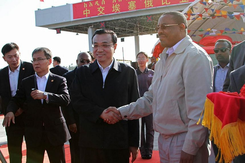 Chinese Premier Li Keqiang (centre left) and Ethiopian Prime Minister Hailemariam Desalegn (centre right) shake hands as they inaugurate the Addis Ababa-Adama expressway in Tulu Dimtu, near Addis Ababa on May 5, 2014. Chinese Premier Li Keqiang