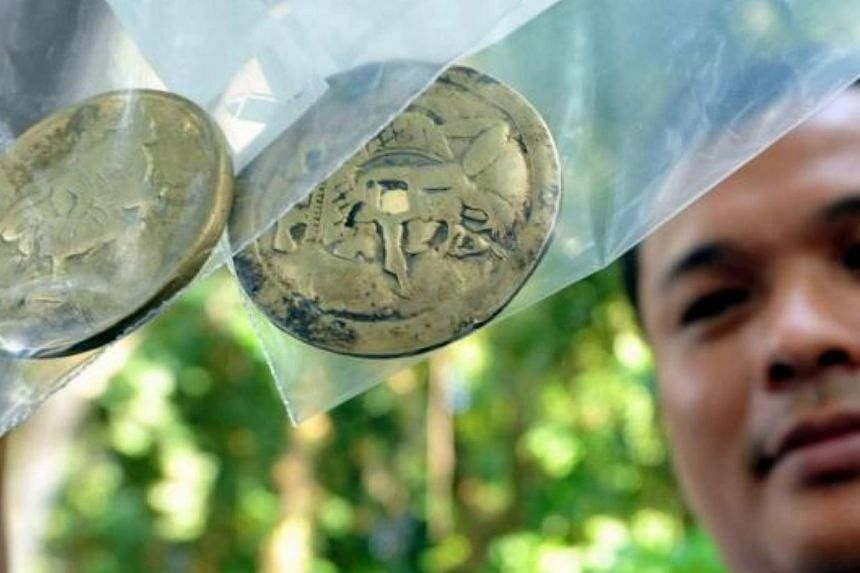 A company employee with the two copper coins unearthed at the site. -- PHOTO: THE STAR/ASIA NEWS NETWORK