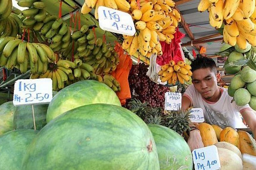 Fruits seller Irwan Syah arranging local fruits at his stall in Jalan Raja Alang near Pasar Chow Kit in Kuala Lumpur. -- PHOTO: THE STAR/ASIA NEWS NETWORK