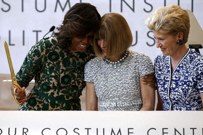 US first lady Michelle Obama (left) embraces US Vogue fashion editor Anna Wintour (centre) at a ceremony to open the Anna Wintour Costume Center at the Costume Institute at the Metropolitan Museum of Art in New York on May 5, 2014. -- PHOTO: REUTERS