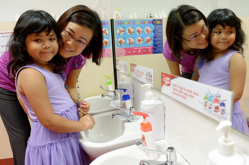Ms Germaine Heng, 47, and her daughter Elizabeth Tai, six, washing their hands at MindChamps pre-school in Paragon. -- PHOTO: BERITA HARIAN