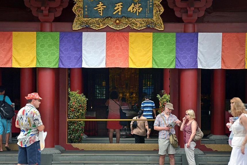 Tourists in front of the Buddha Tooth Relic Temple in Chinatown (top) earlier this year. The Formula One Singapore Grand Prix, which made its debut in 2008, is one of the newer attractions here.
