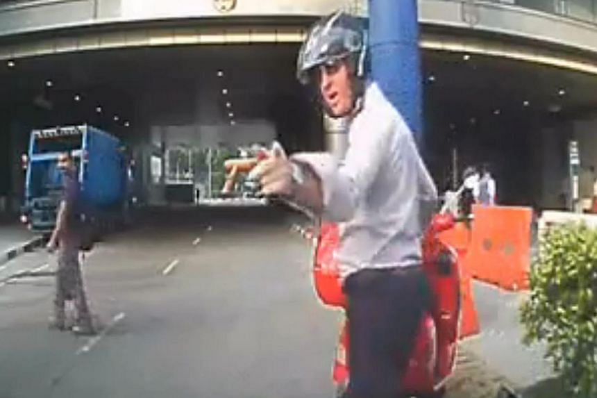 In the video clip, the motorcyclist is seen pointing his finger at the driver of a car at Temasek Boulevard.