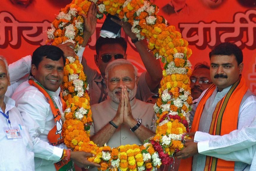 Indian opposition Bharatiya Janata Party (BJP) prime ministerial candidate and Chief Minister of the western state of Gujarat Narendra Modi gestures while garlanded by officials in Jaunpur, India's northern Uttar Pradesh state, on May 5, 2014. India'