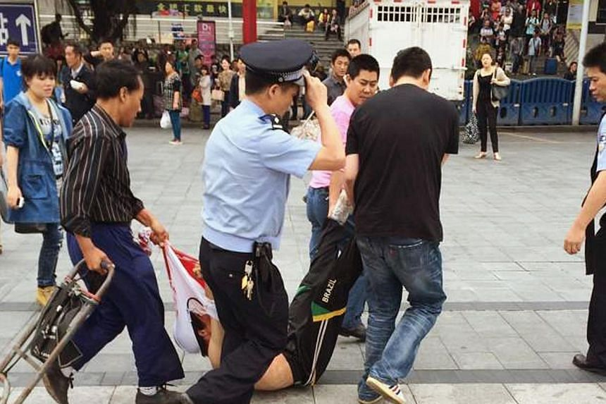 A man, whom local media say is a suspect, is detained after a knife attack at a railway station in Guangzhou, Guangdong province on May 6, 2014. -- PHOTO: REUTERS