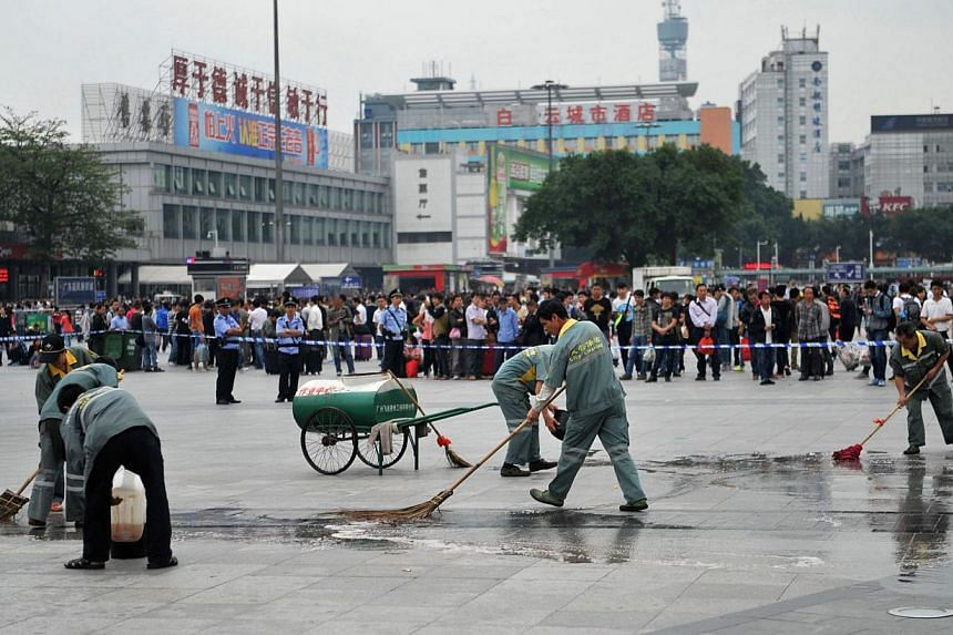 Workers clean the pavement at the scene of a knife attack on the square of Guangzhou railway station in Guangzhou, in southern China's Guangdong province on May 6, 2014. -- PHOTO: AFP