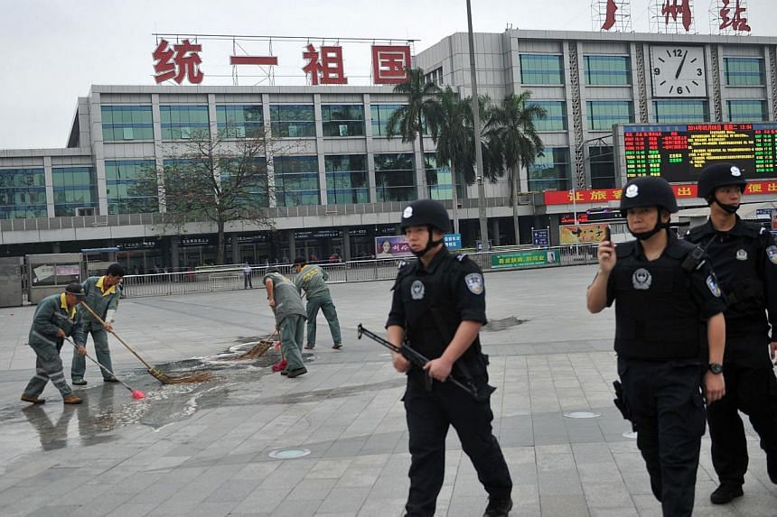 Members of a Chinese SWAT team (right) walk past cleaners (left) removing the blood stains at the scene of a knife attack on the square of Guangzhou railway station in Guangzhou, in southern China's Guangdong province on May 6, 2014. -- PHOTO: AFP
