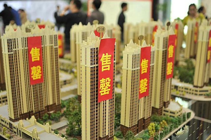 Customers visit a real estate exhibition displaying models of apartments in Hefei, Anhui province, on May 1, 2014. More Chinese cities are rolling out measures to encourage home purchases, in a sign that local governments are increasing efforts to sa