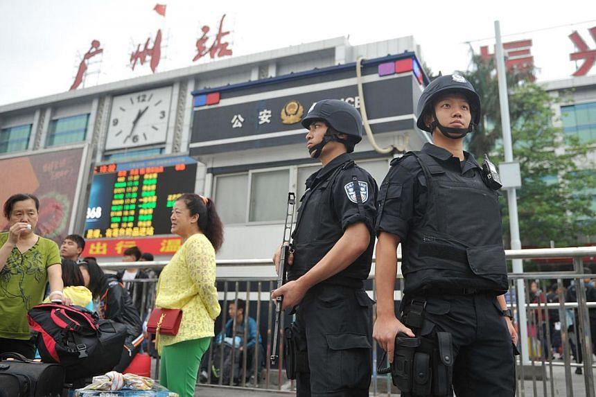 Members of a Chinese SWAT team stand guard on the square of Guangzhou railway station after a knife attack outside the station in Guangzhou, in southern China's Guangdong province on May 6, 2014. Six people were wounded in a knife attack at a railway
