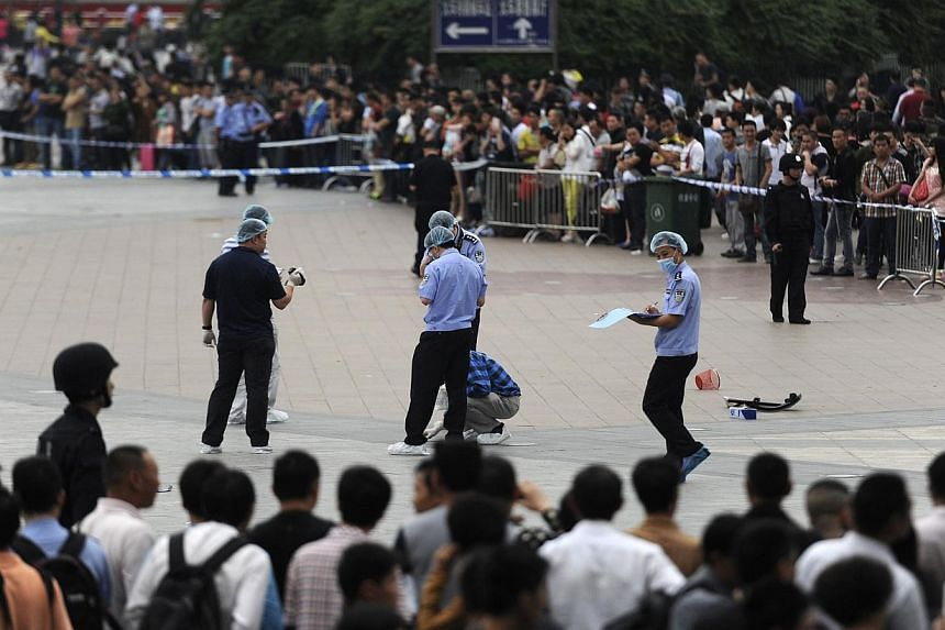 People look on as police officers investigate at the scene after a knife attack at a railway station in Guangzhou, Guangdong province on May 6, 2014. -- PHOTO: REUTERS