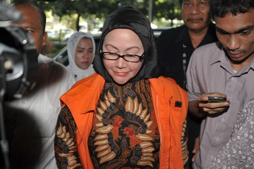 The governor of Banten, Ratu Atut Chosiyah (centre) arrives for her trial at a corruption court in Jakarta on May 6, 2014. Indonesia's first female provincial leader went on trial on Tuesday, accused of bribing one of the country's top judges ove