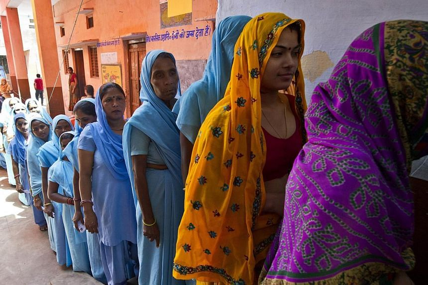 Indian women queue to cast their votes at a polling booth in Alwar on April 24, 2014. India is on course for a record turnout in its general election as a young electorate and women engage with politics more than ever before, with unpredictable resul