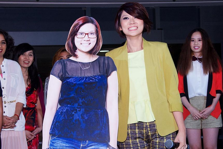 The second runner-up, property officer Chua Tse Lyn, 24, next to her pre-makeover standee, won $1,000 worth of shopping and dining vouchers.-- FILE PHOTO:MARINA SQUARE