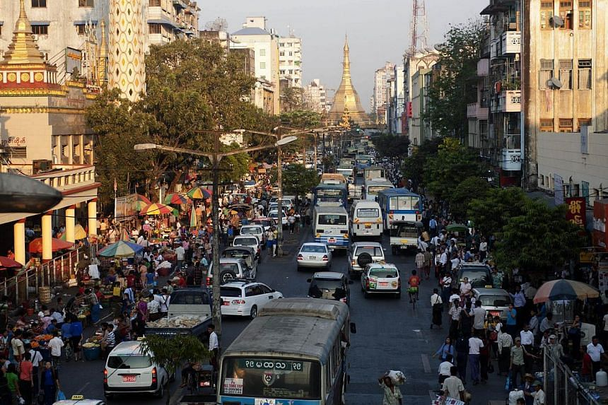 Commuters pass along a busy street in Yangon on March 3, 2014. Corruption is the top concern for businesses in Myanmar, which is undergoing liberal reforms after the end of military rule, according to a UN-led survey released on Tuesday.-- FILE