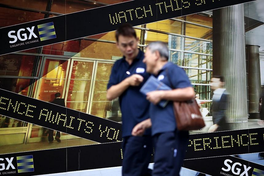 People walk past a logo of the Singapore Stock Exchange (SGX) outside its premises in the financial district of Singapore on April 23, 2014. A group of financial commentators and experts from The Sunday Times and DBS Bank will be speaking at The Sund