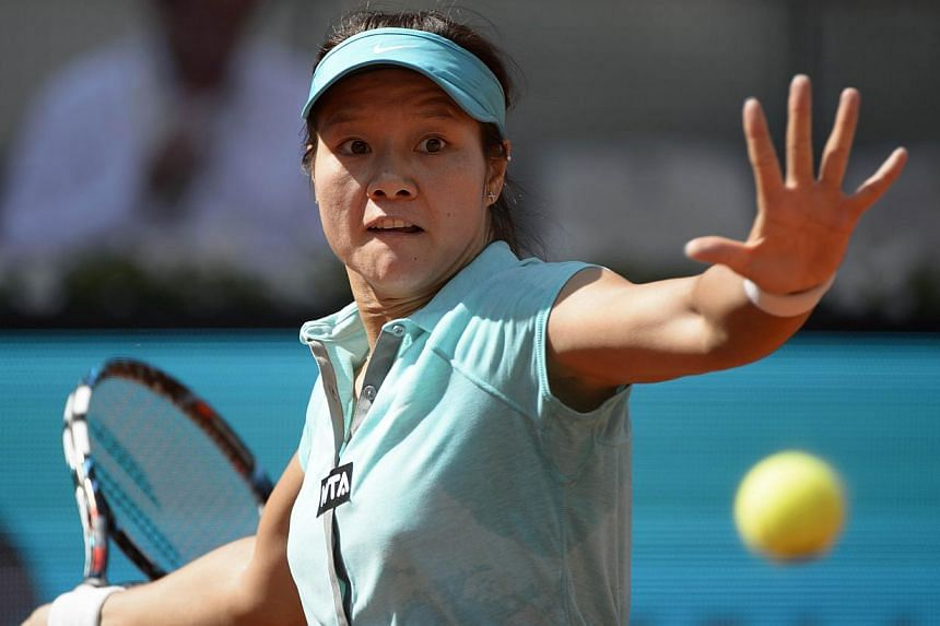Chinese player Li Na returns the ball to Chinese player Zheng Jie during their women's singles second round tennis match of the Madrid Masters at the Magic Box (Caja Magica) sports complex in Madrid on May 6, 2014. Women's tennis' world No. 2 Li Na s