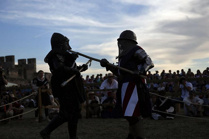 A female fighter from the United States (right) hits her New Zealand opponent with a polearm during a duel at the Medieval Combat World Championship in Belmonte, Spain, on May 1, 2014. -- PHOTO: REUTERS