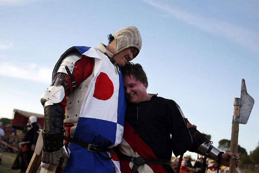 Yasushi Ami from Japan (left) hugs Christoph Unterbuchschachner from Austria after being defeated in their polearm duel at the Medieval Combat World Championship in Belmonte, Spain, May 1, 2014. -- PHOTO: REUTERS
