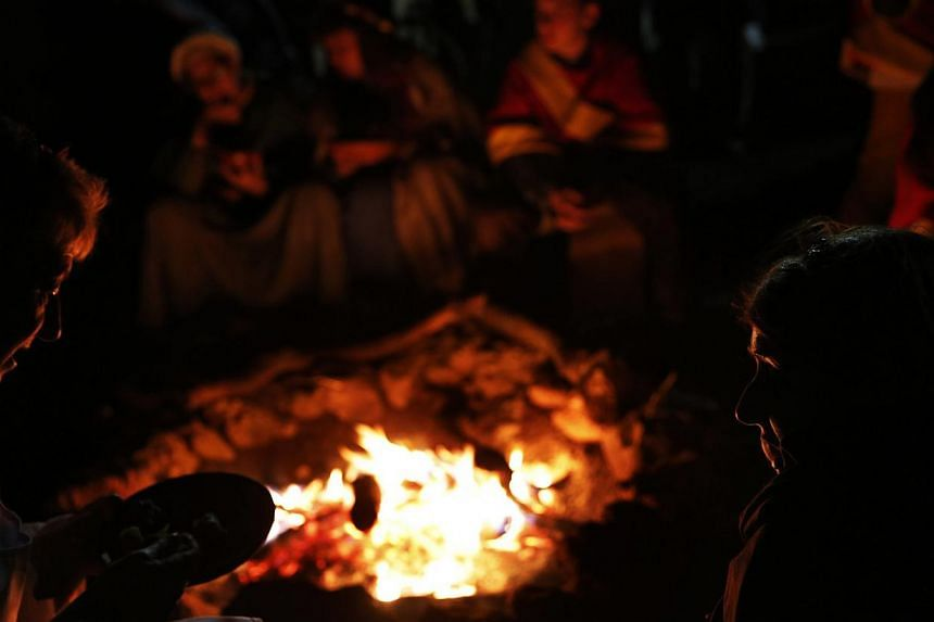 People eat by a bonfire at the camp of the Spanish team during the Medieval Combat World Championship in Belmonte, Spain on May 2, 2014. -- PHOTO: REUTERS