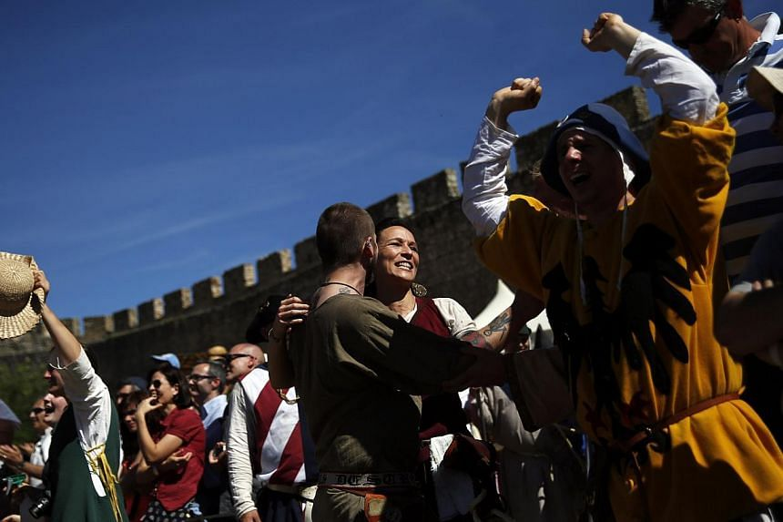 Supporters of the German team celebrate a victory during a competition at the Medieval Combat World Championship in Belmonte, Spain on May 1, 2014. -- PHOTO: REUTERS