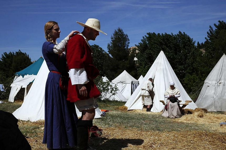 A Polish fighter reacts as a woman looks at his sunburnt neck while resting at their camp during the Medieval Combat World Championship in Belmonte, Spain on May 2, 2014. -- PHOTO: REUTERS