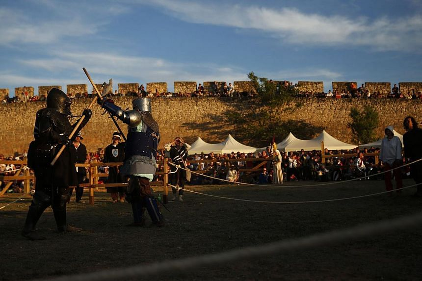 Female fighters from New Zealand (left) and Luxembourg compete in a polearm duel during the Medieval Combat World Championship in Belmonte, Spain on May 1, 2014. -- PHOTO: REUTERS