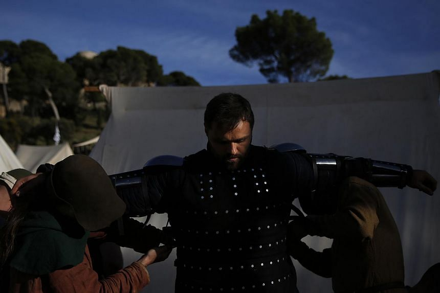 """A fighter from the Spanish team gets help putting on his armour before a """"5 vs 5"""" competition during the Medieval Combat World Championship in Belmonte, Spain on May 2, 2014. -- PHOTO: REUTERS"""