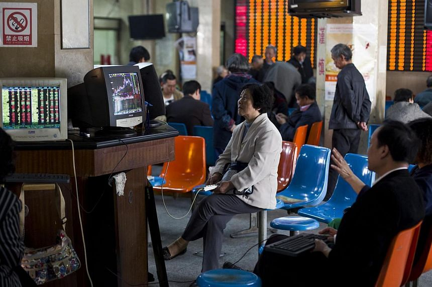 Investors look at computer screens showing stock information at a brokerage house in Shanghai on April 14, 2014. Hong Kong stocks fell on Wednesday as concerns on property and tech valuations hurt investor confidence after a United States tech sell-o
