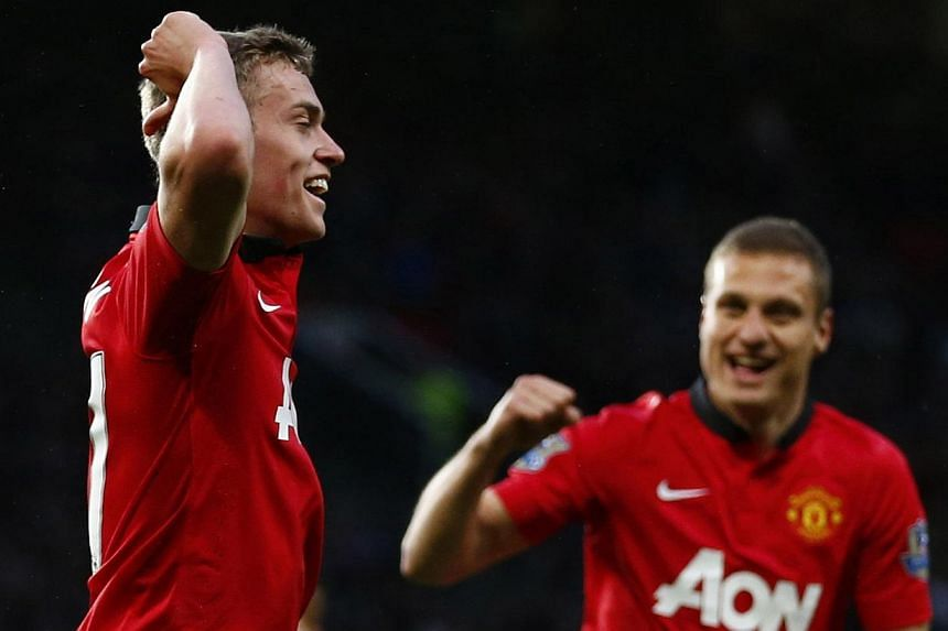 Manchester United's James Wilson (left) celebrates with teammate Nemanja Vidic after scoring a goal against Hull City during their English Premier League soccer match at Old Trafford in Manchester, northern England on May 6, 2014. -- PHOTO: REUTERS