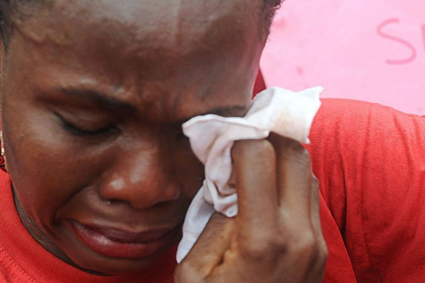One of the mothers of the missing Chibok school girls wipes her tears as she cries during a rally by civil society groups pressing for the release of the girls in Abuja on May 6, 2014, ahead of World Economic Forum. Members of civil society groups ma