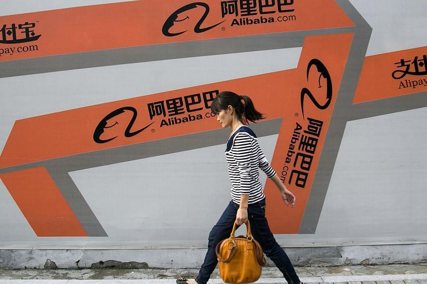 A woman walks past an Alibaba advertisement on a wall in Hangzhou, Zhejiang province on Sept 26, 2013. -- FILE PHOTO: REUTERS