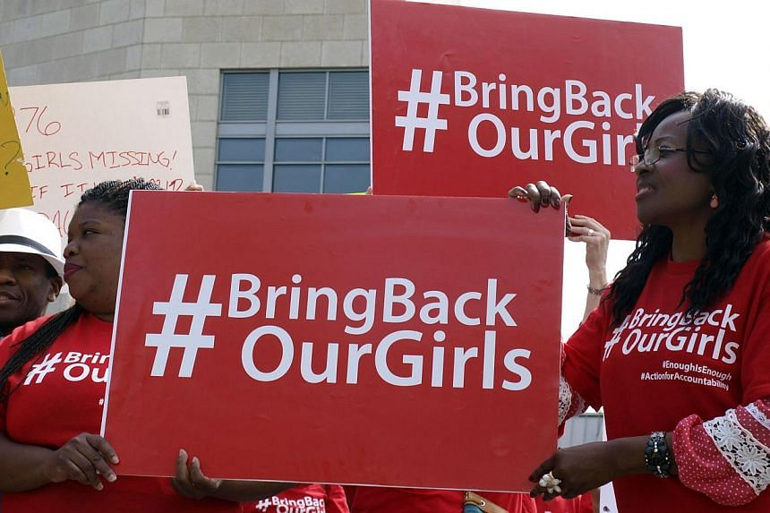 Protestors hold signs during a demonstration on May 6, 2014 outside the Nigerian embassy in Washington,DC demanding robust action to rescue more than 200 schoolgirls kidnapped by Boko Haram militants in the West African country.The United State