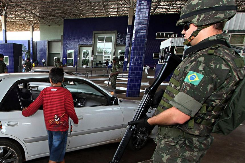 Brazilian Army soldiers stand guard at the Puente de Amistad in Foz do Iguacu, Parana, bordering with Paraguay's Ciudad del Este, during security operations to prevent weapons and explosives smuggling ahead of the upcoming Brazil 2014 Fifa World Cup,