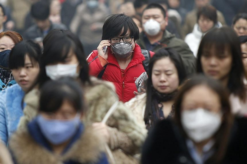 Commuters wearing masks make their way amid thick haze in the morning in Beijing on Feb 26, 2014. About 64 per cent of people in China, the world's biggest polluter, identify themselves as environmentalists, more than double that of Europe and the Un